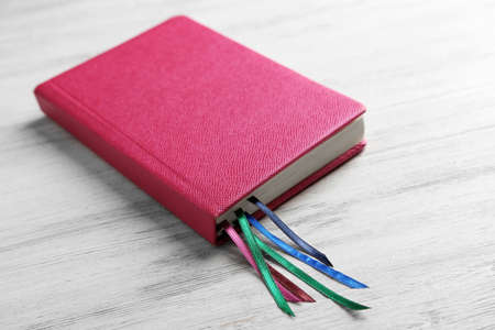 Pink notebook with bookmarks on wooden table