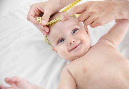 Professional pediatrician examining smiling baby