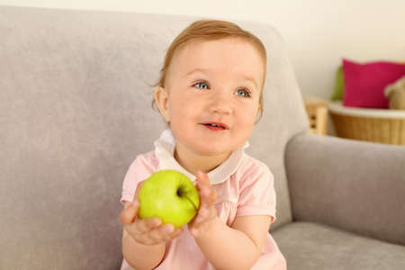 Baby with apple on sofa in room
