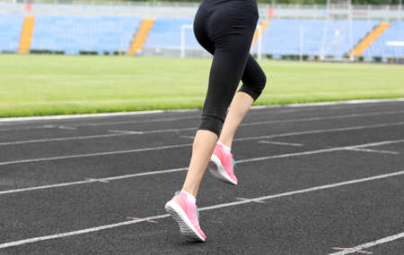 Woman running in pink sneakers on a stadium