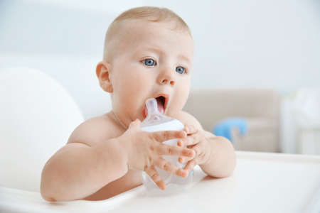 Photo pour Little baby drinking water from bottle indoors - image libre de droit