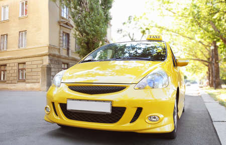 Yellow taxi car on city road