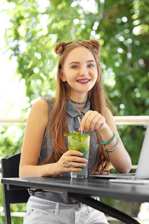 Beautiful teenager girl with laptop and cocktail in cafe
