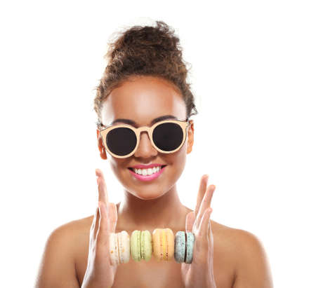 Young woman holding pile of macaroons on white background