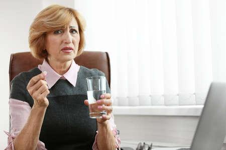 Senior businesswoman taking medicines in office