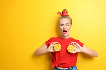 Young beautiful woman with orange on yellow background