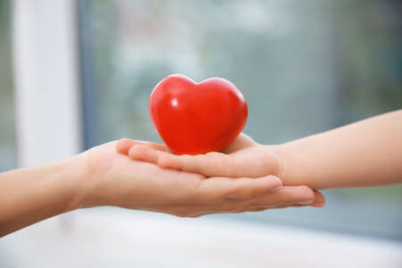 Hands of child and adult woman holding red heart, closeup