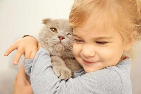 Photo pour Closeup of adorable little girl embracing cute cat in the room - image libre de droit