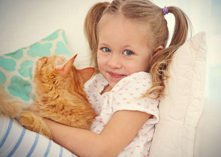 Cute little girl with red cat at home, close up