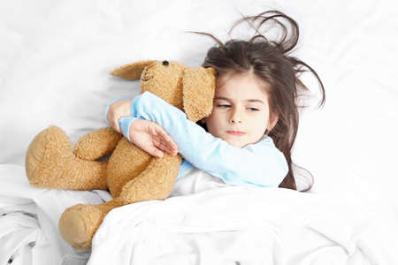 Cute little girl lying in bed with cuddly toy
