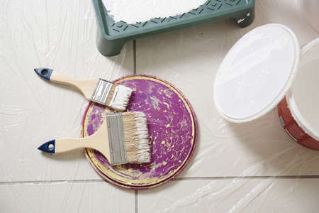 Brushes and cover of plastic bucket with paint on floor