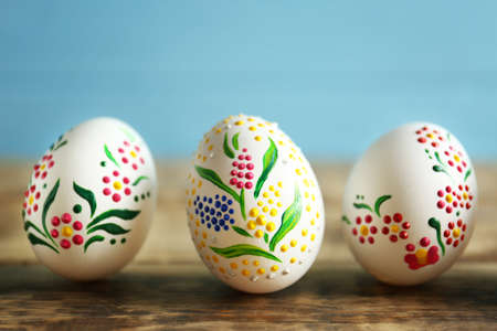 Colourful Easter eggs with floral ornament in a row on wooden table and blue background, closeup