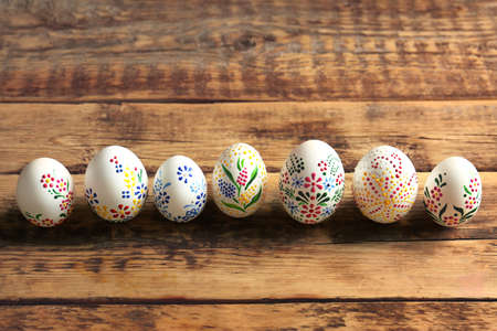Colourful Easter eggs with floral ornament in a row on wooden background