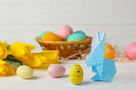 Easter bunny with colorful eggs on wooden table against light background
