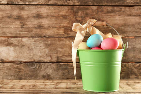 Metal bucket with colorful Easter eggs on wooden table