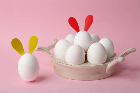 Easter eggs with funny decor on color background
