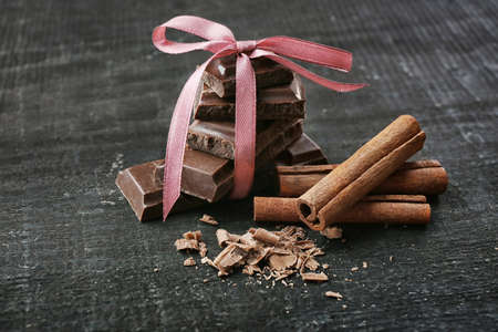Broken chocolate pieces and cinnamon sticks on wooden background