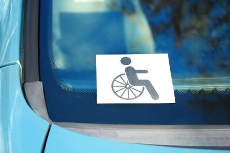Symbol of handicapped on car windshield, closeup