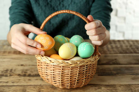 Woman with Easter eggs in basket at wooden table