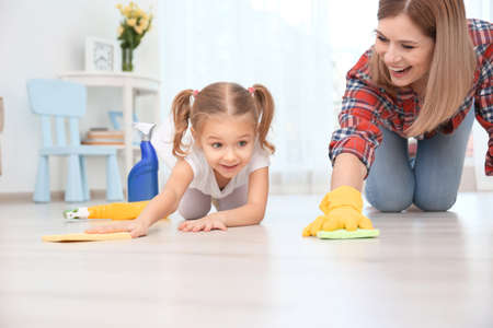 Photo pour Little girl and her mother cleaning floor at home - image libre de droit