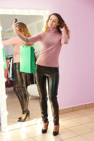 Beautiful young woman taking selfie in modern shop