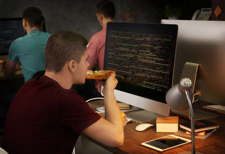 A young programmer eating pizza while working in the office