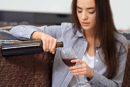 Photo pour Depressed woman drinking wine indoors - image libre de droit