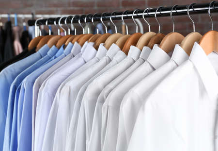 Rack of clean clothes hanging on hangers at dry-cleaning