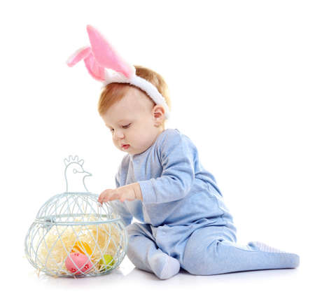 Cute little baby in bunny ears and decorative basket with Easter eggs isolated on white