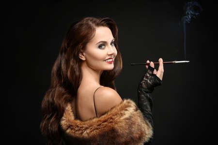 Beautiful woman smoking cigar on dark background