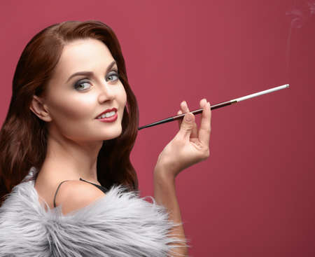 Beautiful woman smoking cigar on color background