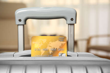 Credit card in suitcase on blurred background