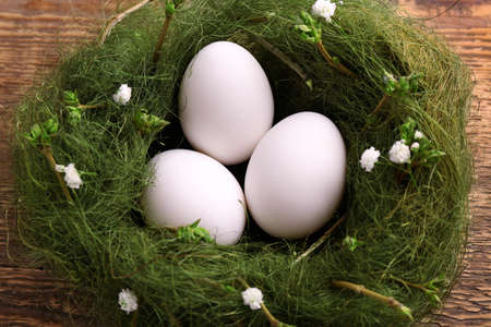 Easter eggs in nest decorated with flowers, closeup