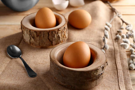 Wooden stands with Ester eggs on linen tablecloth
