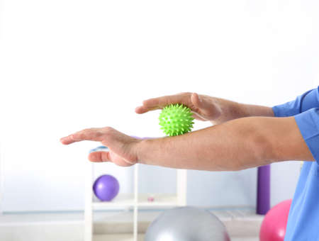 Man doing exercises with stress ball in clinic