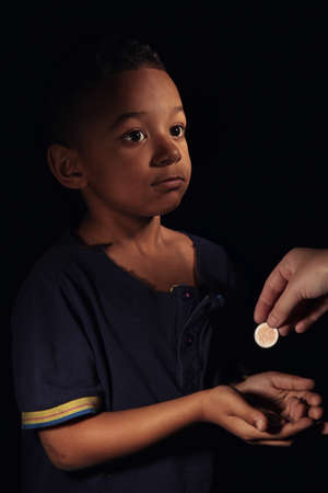 Cute little boy asking for handout on dark background. Poverty concept