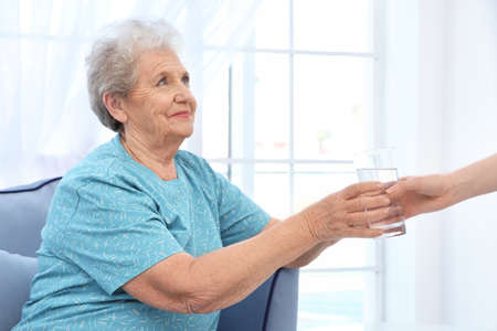 Young lady giving glass of water to elderly woman. Concept of nursing