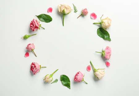 Foto de Beautiful flowers and green leaves as floral frame on white background - Imagen libre de derechos