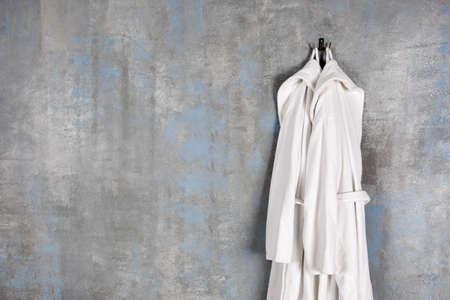 Bathrobes hanging on grey wall