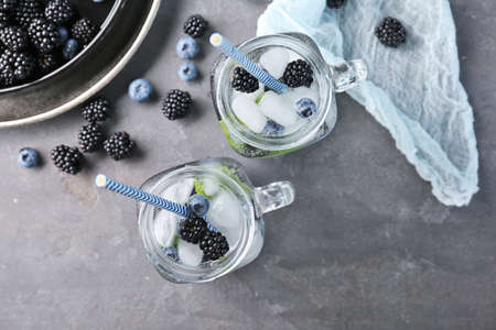 Refreshing water with blackberries and blueberries in mason jars on table