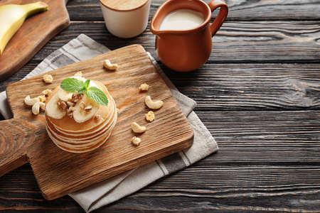 Yummy banana pancakes on wooden board