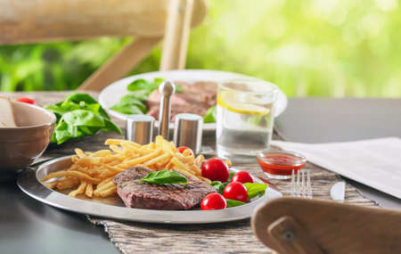 Silver plate with delicious steak and fries on table in restaurant