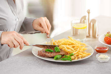 Woman eating delicious grilled steak with fries in restaurant