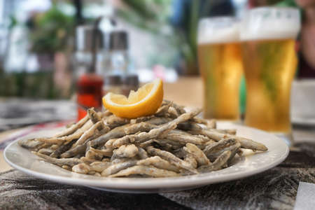 Plate with fried anchovies on table in restaurant