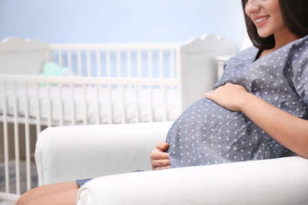 Pregnant woman sitting in armchair near baby crib at home