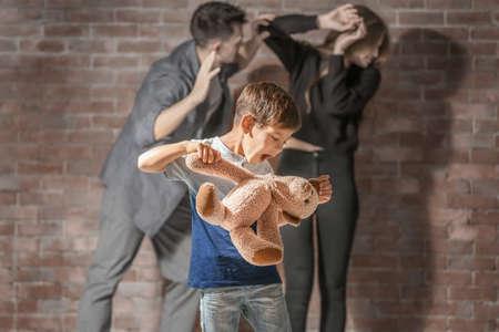 Little boy punishing teddy bear while parents having fight on background