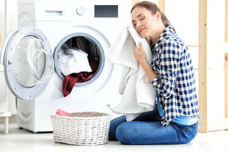 Photo for Young woman doing laundry at home - Royalty Free Image