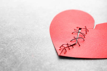Photo pour Paper heart cut in half and sewn back together on light background. Relationship problems - image libre de droit
