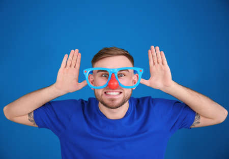 Young man in funny disguise posing on color background. April fool's day celebration