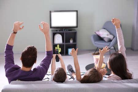 Photo pour Family watching TV on sofa at home - image libre de droit